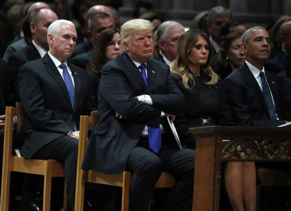 President Donald Trump crosses his arms as he listened as Brian Mulroney, former Prime Minister of Canada spoke during the State Funeral for George H.W. Bush at the Washington National Cathedral, Wednesday, Dec. 5, 2018, in Washington.