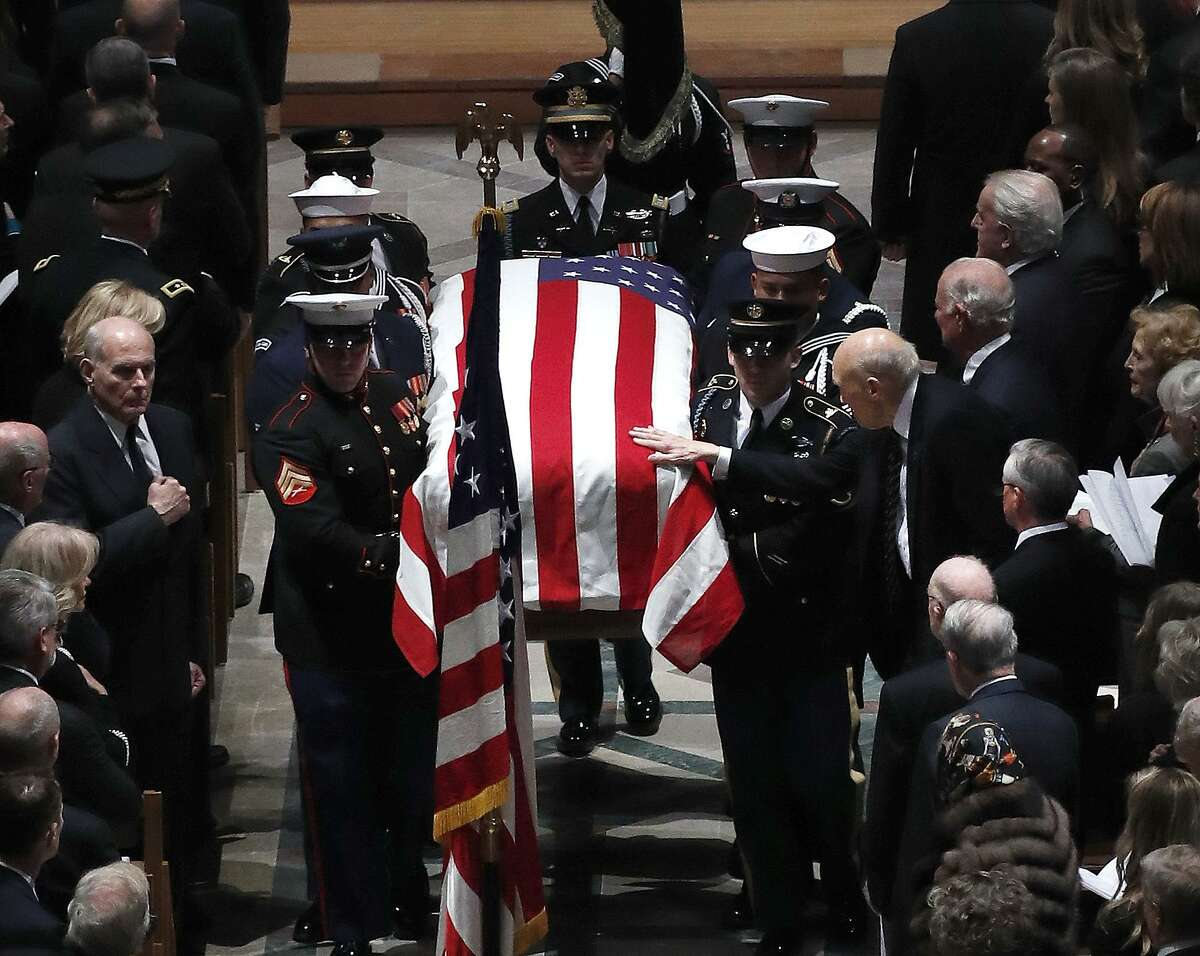 Alan K. Simpson, former US Senator from Wyoming reaches out to touch the flag draped casket of at the end of the State Funeral for George H.W. Bush at the Washington National Cathedral, Wednesday, Dec. 5, 2018, in Washington.
