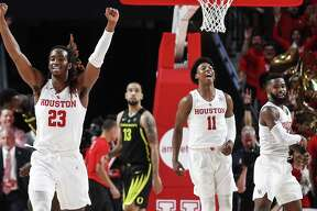 Houston forward Cedrick Alley Jr. (23), guard Nate Hinton (11) and guard Corey Davis Jr. (5) celebrate the Cougars' 65-61 win over then-No. 18 Oregon in the Cougars' first game at the Fertitta Center on Dec. 1.
