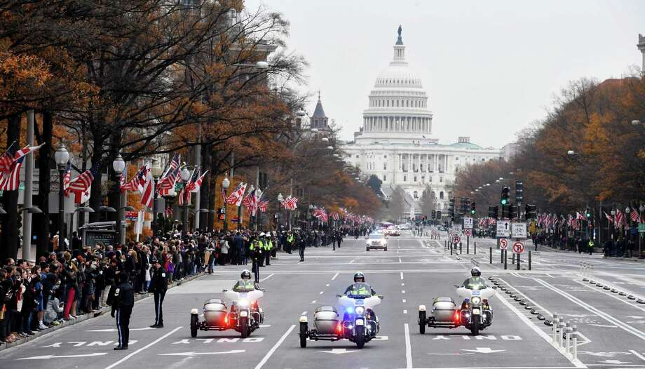 People gather along Pennsylvania Avenue to pay their respects as the motorcade with the hearse carrying the remains of President George H.W. Bush left the Capitol and made its way to the National Cathedral for a funeral service there Dec. 5, 2018 in Washington. Photo: Washington Post Photo By Katherine Frey / The Washington Post