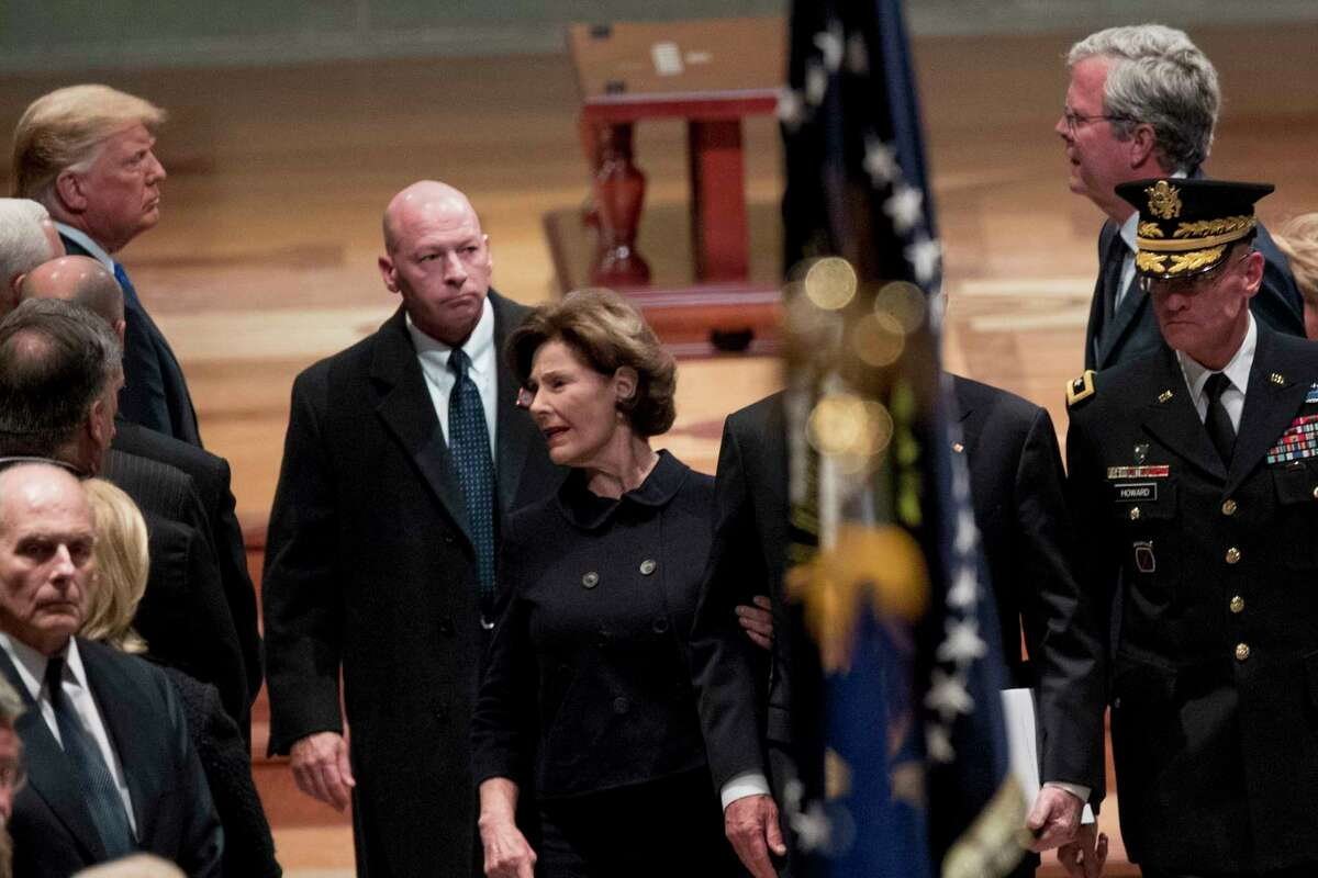President Donald Trump, left, looks at former Florida Gov. Jeb Bush, right, as Bush family members follow the flag-draped casket of former President George H.W. Bush as he is carried out by a military honor guard during a State Funeral at the National Cathedral, Wednesday, Dec. 5, 2018, in Washington. Also pictured is President Donald Trump's Chief of Staff John Kelly, bottom left, and former first lady Laura Bush, center. (AP Photo/Andrew Harnik, Pool)