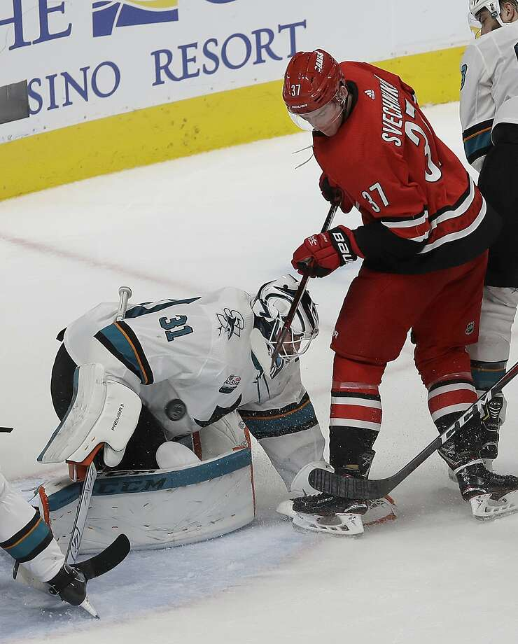 Sharks goalie Martin Jones covers the puck as Hurricanes right wing Andrei Svechnikov lurks near the crease. Photo: Jeff Chiu / Associated Press