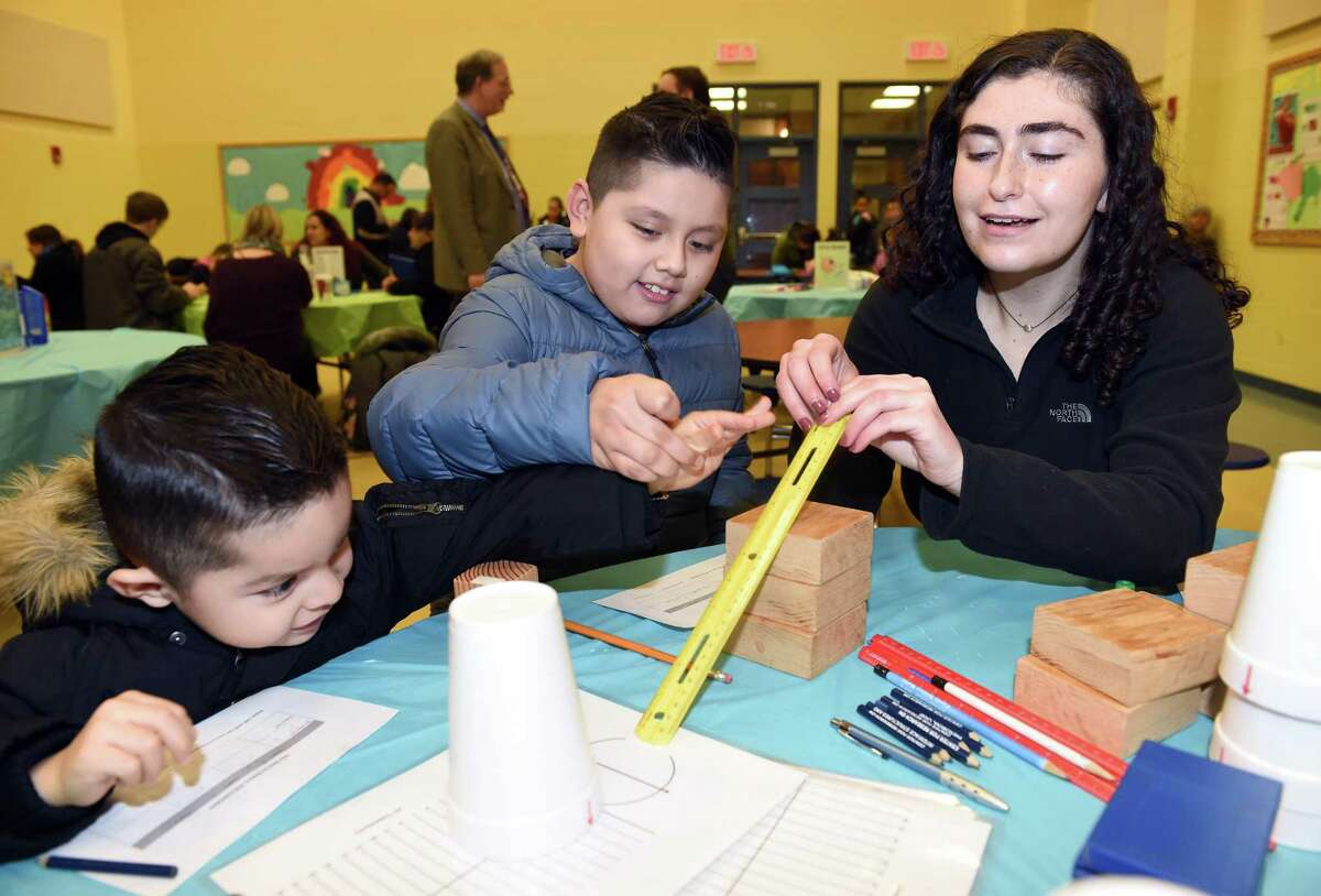 From left, John Lopez, 3, and his brother, Jason, 9, learns how experiments work with Southern Connecticut State University sophomore Amy Orenstein at Family Science Night at Hill Central School in New Haven on Dec. 5, 2018.