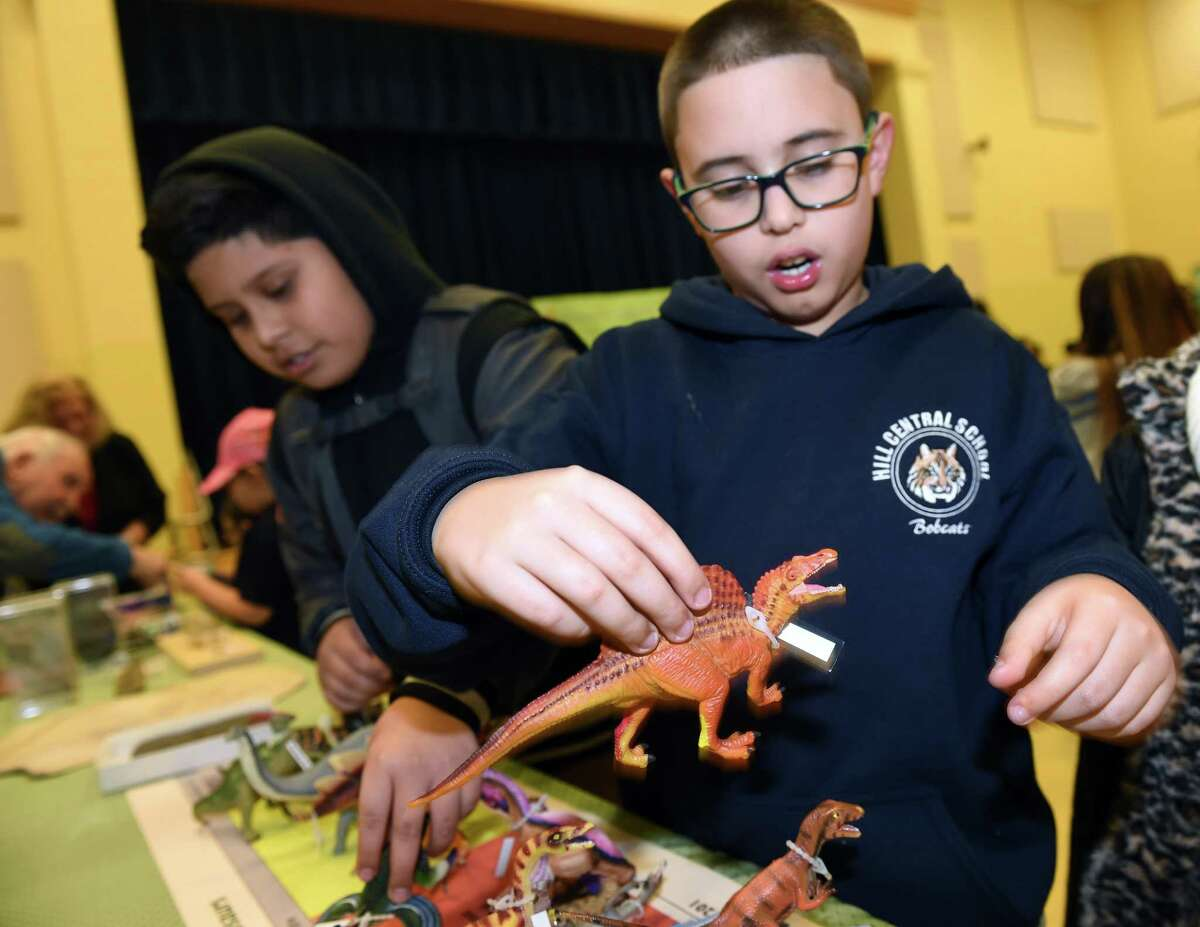 Third grader Elvin Mercado, 8, plays with a spinosaurus at a Yale Peabody Museum display at Family Science Night at Hill Central School in New Haven on Dec. 5, 2018.