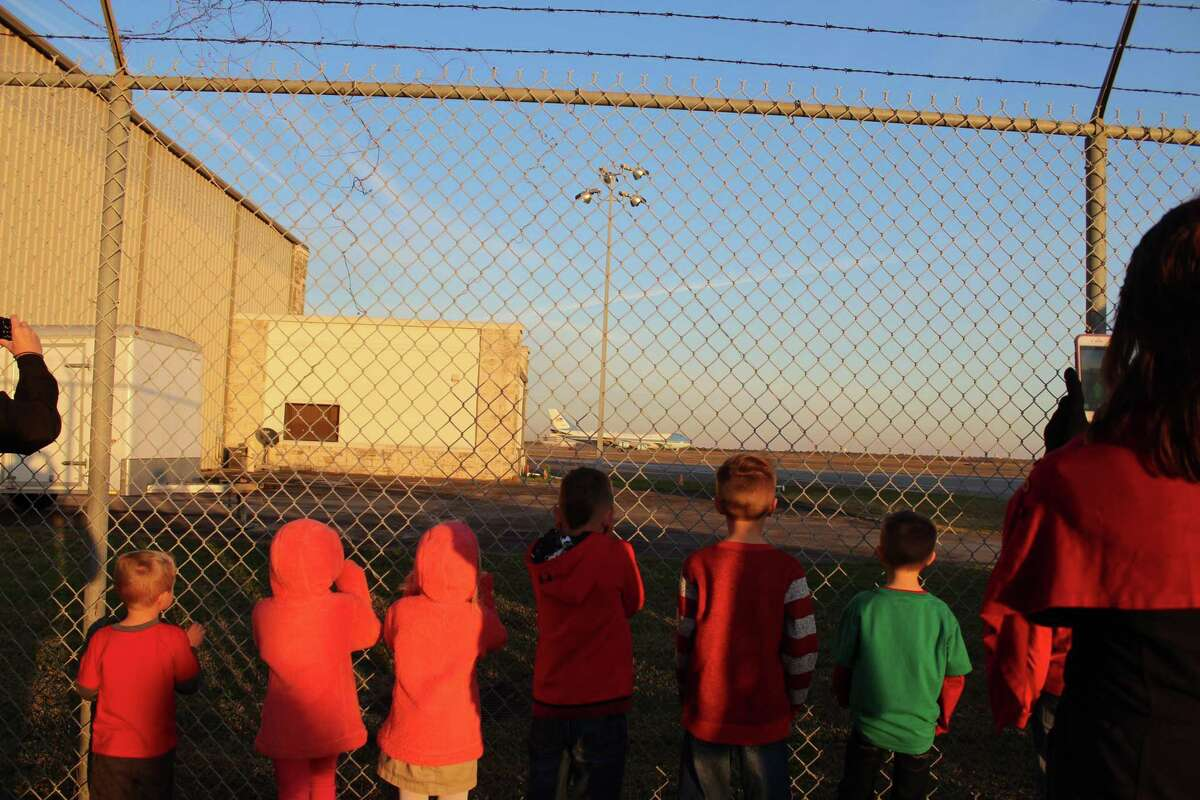 Children watch through a fence at Ellington Airport as the remains of George H.W. Bush return to Houston. Many residents brought their children, saying they wanted them to witness the event.