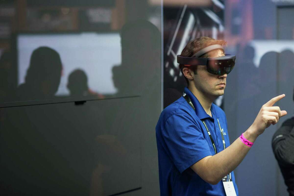 An attendee wears a Microsoft Corp. HoloLens headset during the Microsoft Developers Build Conference in Seattle, Washington, U.S., on Monday, May 7, 2018. The Build conference, marking its second consecutive year in Seattle, is expected to put emphasis on the company's cloud technologies and the artificial intelligence features within those services. Photographer: Grant Hindsley/Bloomberg