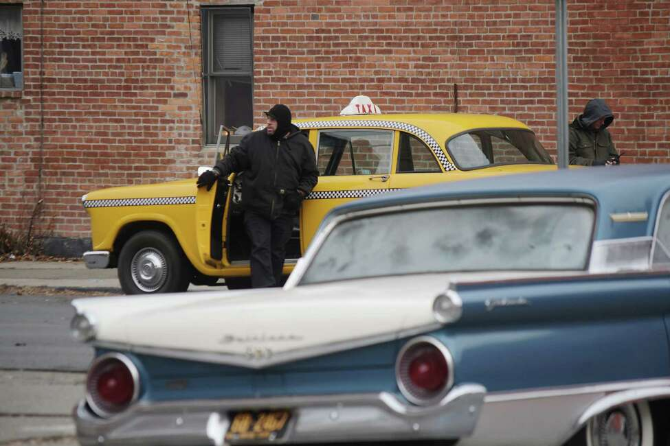 Film crew members move older style vehicles into positions for filming a street scene along Jefferson Street during filming for a movie on Thursday, Dec. 6, 2018, in Troy, N.Y. (Paul Buckowski/Times Union)