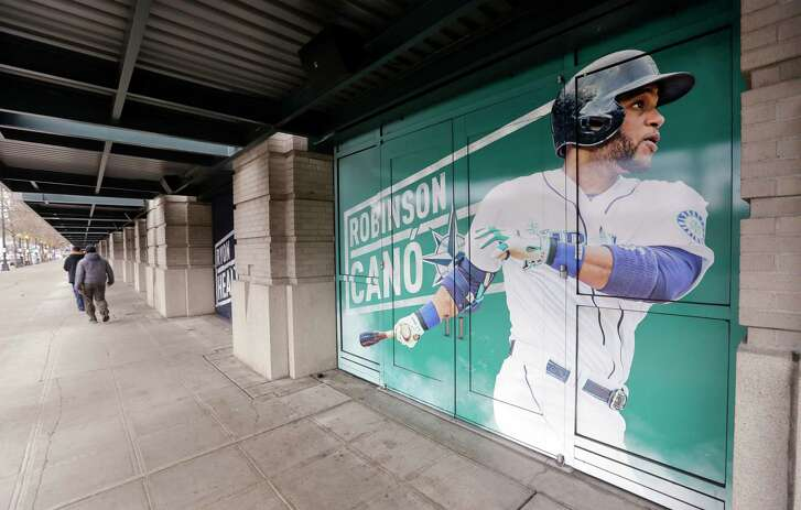 In this photo taken Thursday, Nov. 29, 2018, an oversized photo of Seattle Mariners' Robinson Cano stands along a sidewalk at the team's ballpark in Seattle. In a deal announced Monday, Dec. 3, 2018, the New York Mets have acquired longtime star second baseman Cano and major league saves leader Edwin Diaz from the Seattle Mariners in a seven-player trade. (AP Photo/Elaine Thompson)