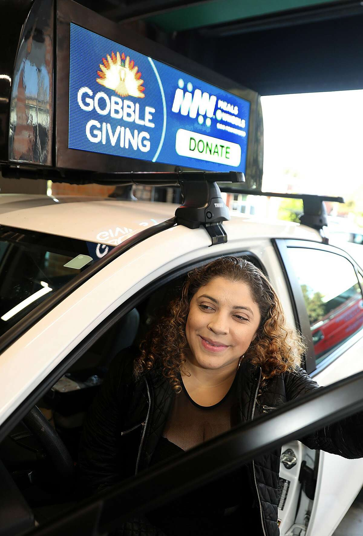 Uber and Lyft driver Jackeline Arana has her car outfitted with display at Firefly on Wednesday, Nov. 28, 2018, in San Francisco, Calif. Firefly makes video advertising screens to place on top of Uber/Lyft cars.