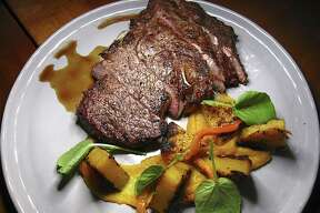 Grilled Dean & Peeler Meatworks rib-eye steak with roasted sweet peppers and butternut squash from Meadow Neighborhood Eatery + Bar.