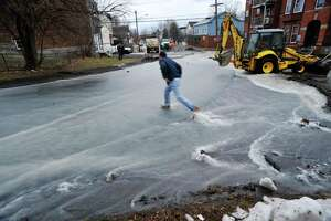 Workers used gravel to try and divert the flowing water away from homes along 4th Ave. and keep the water in the street which was flooded following a water main break in the area of 125th Street and 5th Ave. on Sunday morning, Jan. 17, 2016, in Troy, N.Y.  (Paul Buckowski / Times Union)