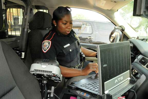 Tomball Police Department officer Cleo Thomas checks the computer in her patrol SUV as she prepares to leave on patrol. The Tomball City Council approved the purchase of a new computer assisted dispatch on Monday.