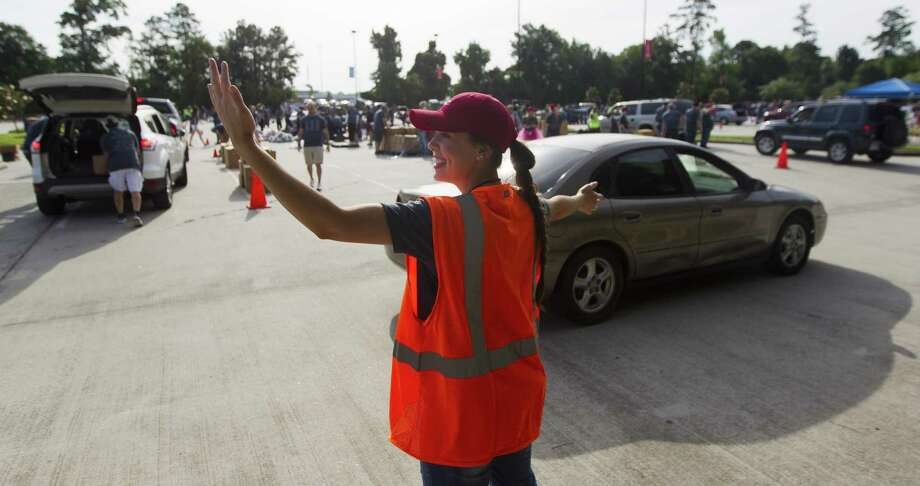 Megan Adams helps direct traffic during The Ark Church's annual spring giveaway that provided 300,000 pounds of food for people in need, Saturday, April 28, 2018, in Conroe. Photo: Jason Fochtman, Staff Photographer / Houston Chronicle / © 2018 Houston Chronicle