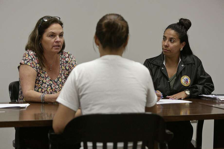 In Restore Court, Judge Lisa Jarrett, left, helps the young survivors of sex-trafficking get the services they need to overcome trauma. Juvenile probation officer Rosalie Vogt, right, listens as Jarrett talks to a young woman about her recent progress in the program. Photo: Lisa Krantz /Staff Photographer / San Antonio Express-News