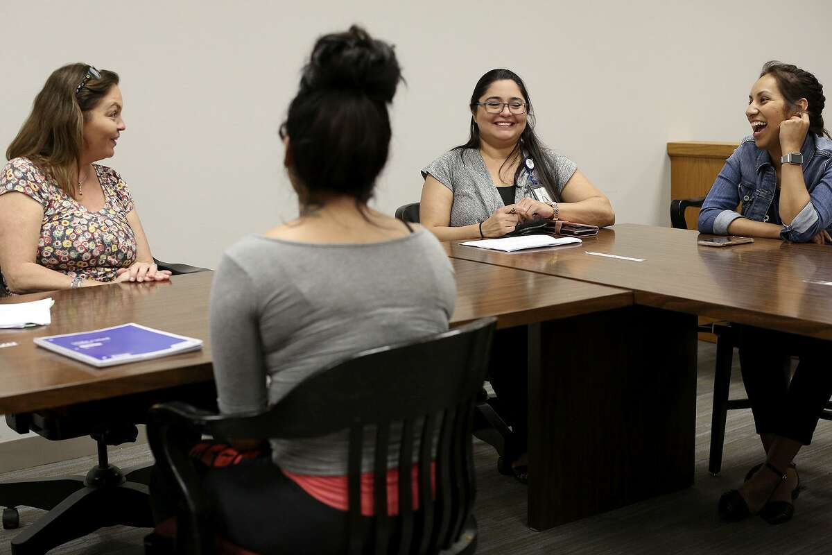 Judge Lisa Jarrett, from left, Ana Martinez, a juvenile probation officer, and Cassandra Limon, a therapist with ChildSafe, talk with a young woman who is a participant in Restore Court.