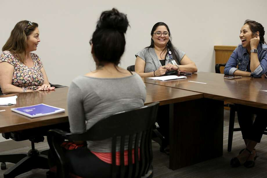 Judge Lisa Jarrett, from left, Ana Martinez, a juvenile probation officer, and Cassandra Limon, a therapist with ChildSafe, talk with a young woman who is a participant in Restore Court. Photo: Lisa Krantz /Staff Photographer / San Antonio Express-News