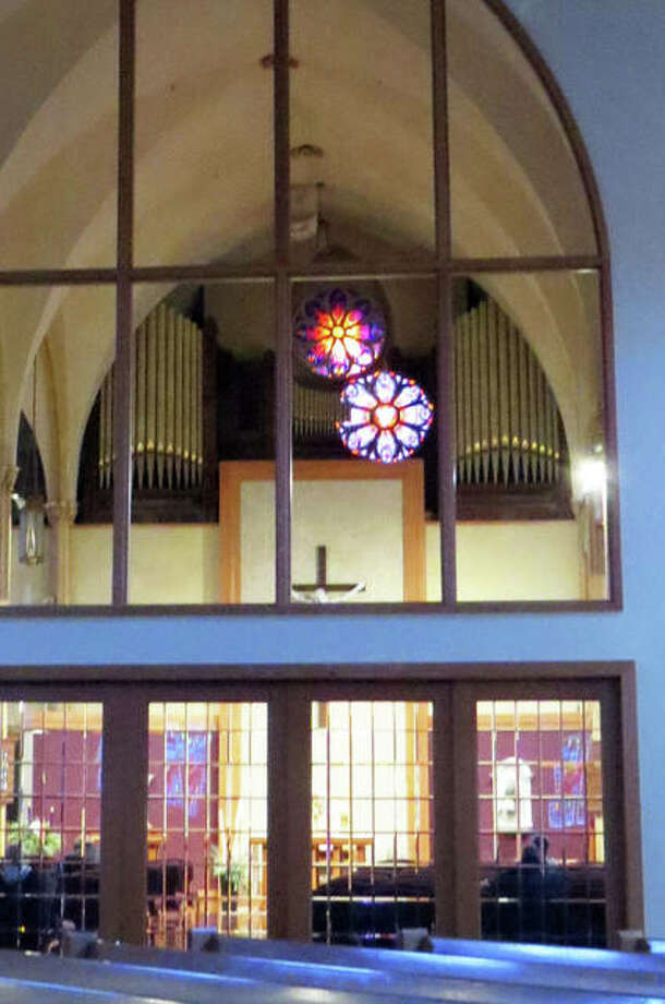 """The old and the new meet at St. Boniface Church in Edwardsville as the rose window from the new addition to the church is reflected under the rose window from the old church. St. Boniface Church is celebrating its 150th anniversary in 2019, with the """"Year of Jubilee"""" celebration. Photo: Carol Arnett