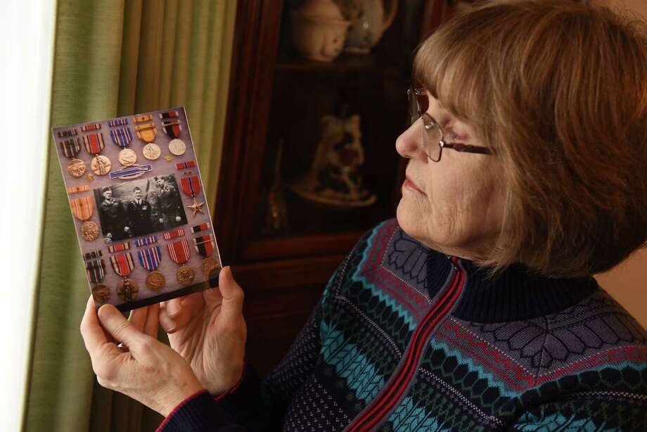 Eileen O'Dea Roach holds a photo of medals and a photo of brother Edward O'Dea, left, her father Leo Patrick O'Dea, middle and her brother Gerald at her home on Thursday, Dec. 6, 2018 in Albany, N.Y. Eileen is the younger sister of Pearl Harbor survivor Edward O'Dea and has complied pages and pages of family history. (Lori Van Buren/Times Union) Photo: Lori Van Buren, Albany Times Union / 20045654A