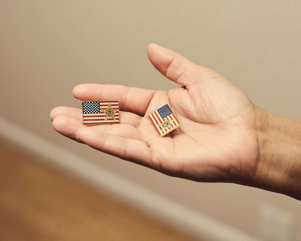 Victorina Morales holds American flag pins with a Secret Service logo, which she said she was asked to wear during President Donald Trump's visits to the Trump National Golf Club in Bedminster, N.J., at her home in Bound Brook, N.J., Nov. 2, 2018. At the president's New Jersey golf course, Morales, an undocumented immigrant, has worked as a maid since 2013. She said she never imagined she