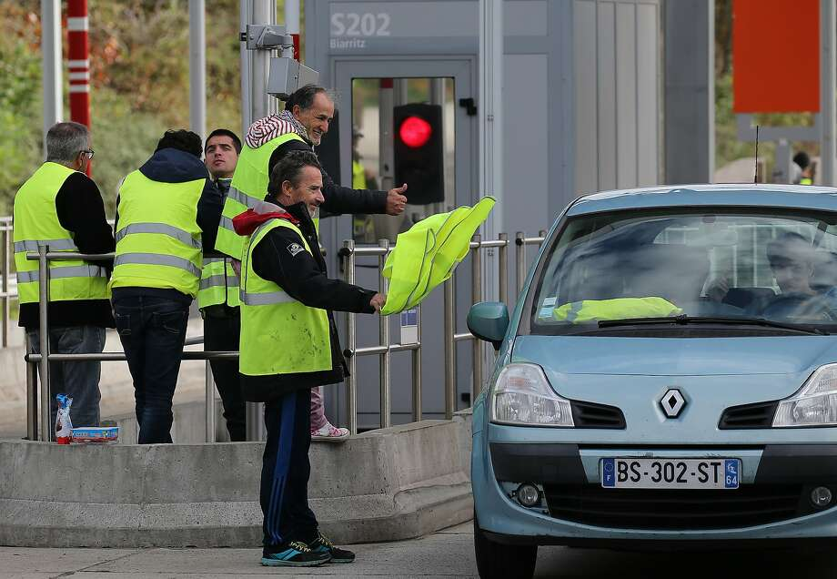 """Yellow vest"" demonstrators man a highway toll gate in Biarritz, France. Police are bracing for more violence despite President Emmanuel Macron's surrender over a fuel tax hike. Photo: Bob Edme / Associated Press"