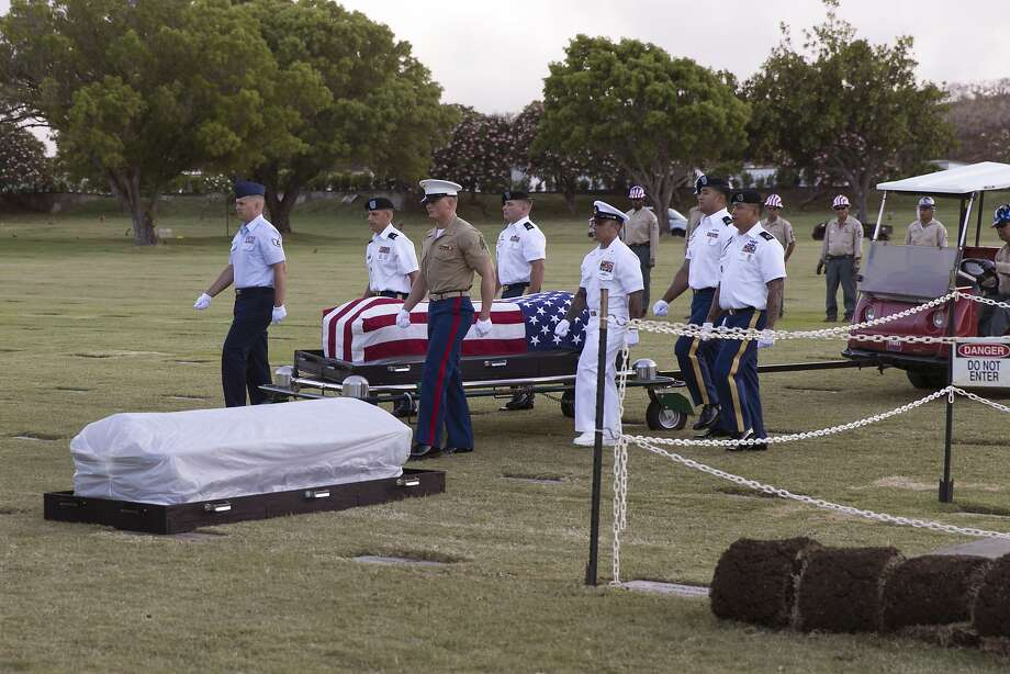 Pallbearers escort the exhumed remains of crew members of the Oklahoma killed in the bombing of Pearl Harbor. Photo: Marco Garcia / Associated Press