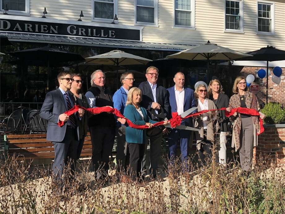 Town officials and the owners of the Darien Grille pose for the chamber of commerce ribbon cutting ceremony. Photo: /contributed Photo