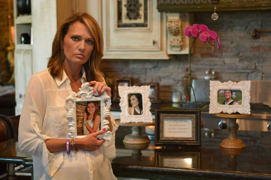 Kim Hess, at her home in The Woodlands, holds a photo of her daughter Cassidy, a student and varsity cheerleader at College Park High School that committed suicide in December 2015. A production that Jodie Schrier first wrote 20 years ago, Hope for the Holidays, will be performed Dec. 15 at The Woodlands College Park High School. It will benefit the nonprofit Cassidy Joined for Hope, which raises awareness about teenage suicide. Photo: Jerry Baker, Freelance / For The Houston Chronicle