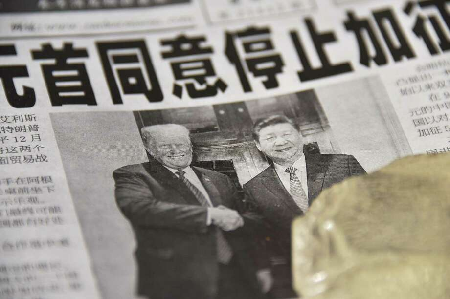 "A newspaper featuring a front page story about the meeting between US President Donald Trump and Chinese President Xi Jinping as seen at a news stand in Beijing on December 3, 2018. - The headline says the two leaders agreed not to increase tarrifs. China's state-run media hailed the trade war truce with the United States as ""momentous"" on December 3 but warned of complex negotiations ahead, even as President Donald Trump said Beijing agreed to cut car tariffs. Since then there has been a new round of tariffs and counter tariffs proposed and businesses are lobbying the Trump administration to halt more tariffs on an additional $300 billion of Chinese imports. (Photo by GREG BAKER / AFP)GREG BAKER/AFP/Getty Images Photo: GREG BAKER, Contributor / AFP/Getty Images / AFP or licensors"
