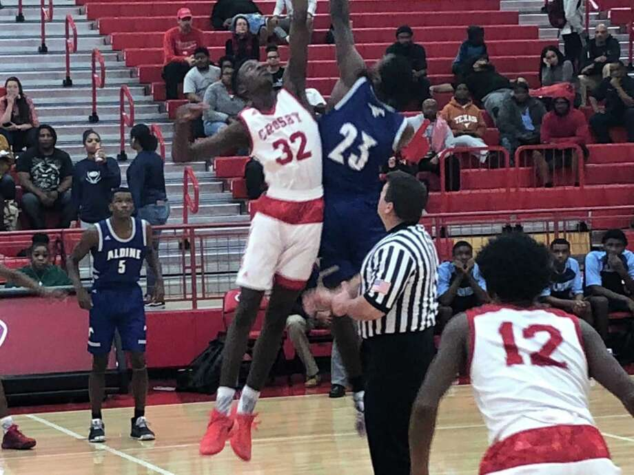 Crosby's Jaydon Samuel (32, white) goes up for the tip-off at the start of a game against Aldine on Dec. 4 at Crosby Photo: Elliott Lapin / Staff Photo