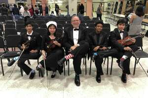 Shown with their crazy socks in honor of President Bush are, from left, orchestra students Neel Jhangiani, Tiffany Nguyen, Director Brian Runnels, Anthony Duke and Brandon Musngi. The 41st president George H. W. Bush was known for his colorful socks.
