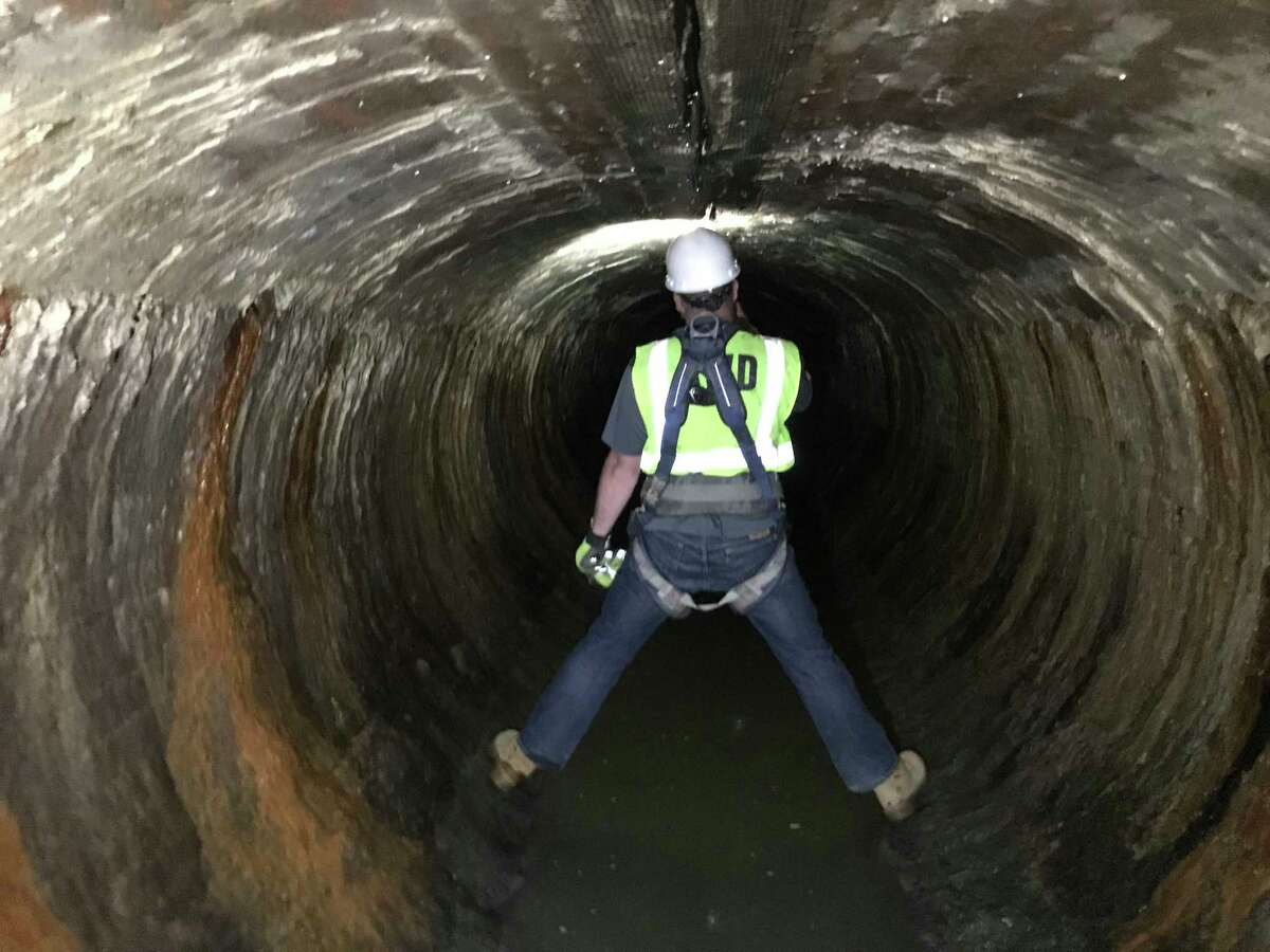 A worker examines a section of century-old drinking water supply transmission line that was patched using a sprayed concrete technology that could extend the life of the pipe by another five decades.
