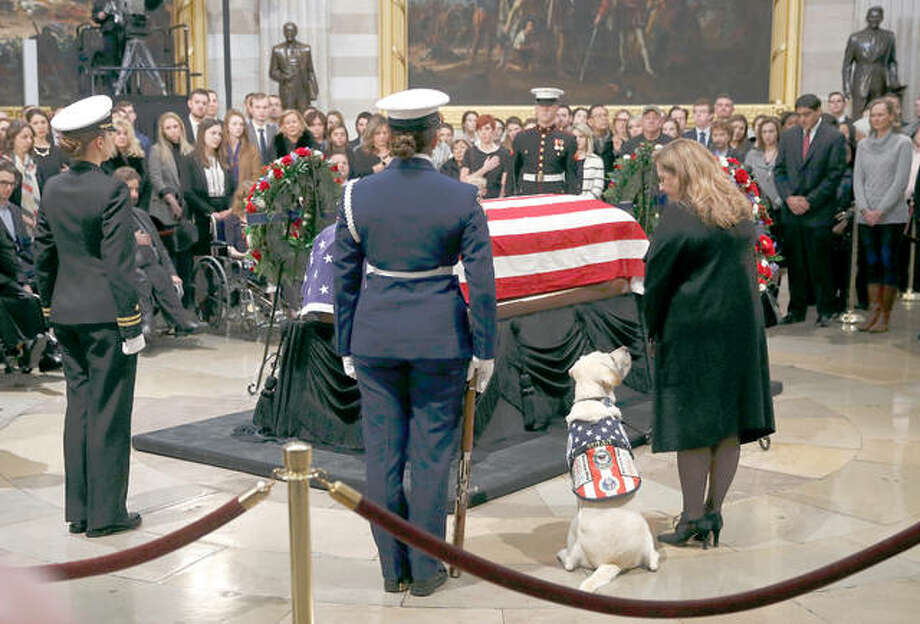 Sully, the service dog of former President George H.W. Bush, sits alongside Valerie Cramer as they visit the flag-draped casket of President Bush in the Capitol Rotunda in Washington, Tuesday, Dec. 4, 2018. Wood River native Karly Schley, a member of the U.S. Coast Guard Ceremonial Honor Guard, stands in the foreground. Schley worked multiple shifts guarding the former president's casket as it sat at the National Cathedral. Photo: AP Photo/Patrick Semansky