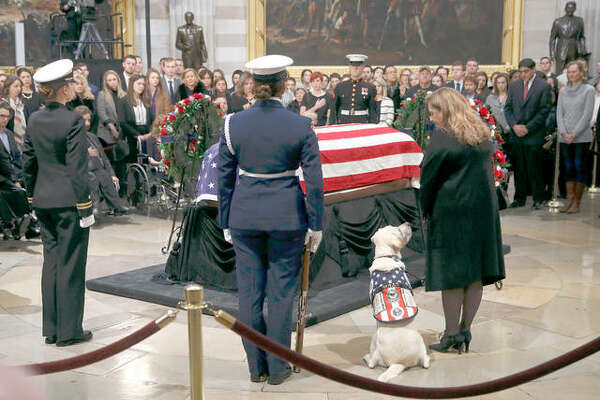 Sully, the service dog of former President George H.W. Bush, sits alongside Valerie Cramer as they visit the flag-draped casket of President Bush in the Capitol Rotunda in Washington, Tuesday, Dec. 4, 2018. Wood River native Karly Schley, a member of the U.S. Coast Guard Ceremonial Honor Guard, stands in the foreground. Schley worked multiple shifts guarding the former president's casket as it sat at the National Cathedral.