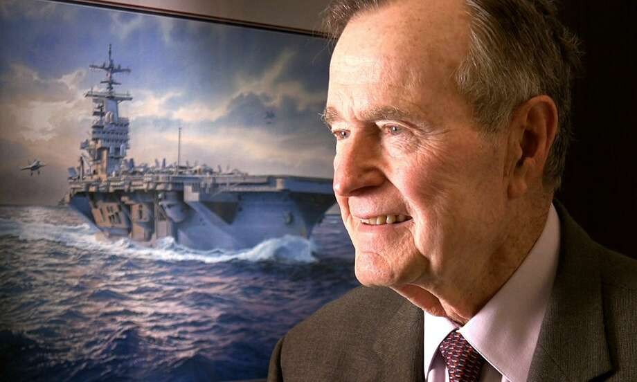 Former President George H.W. Bush is seen at his Houston office. Behind him is a portrait of the USS George H.W. Bush.