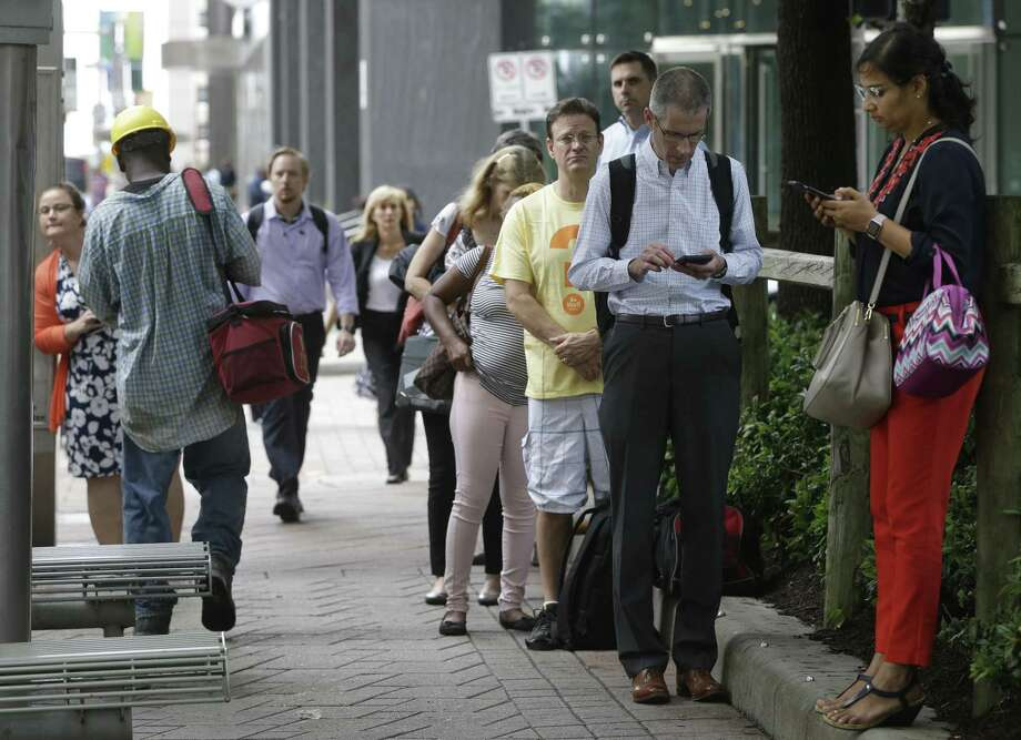 Passengers, many with smart phones in hand, wait at a Metropolitan Transit Authority bus stop at Louisiana and Walker on July 11, 2017, in downtown Houston. Metro in 2019 will conduct a six-month test offering internet access on two bus routes and a light rail line. Photo: Melissa Phillip, Staff / Houston Chronicle / © 2017 Houston Chronicle