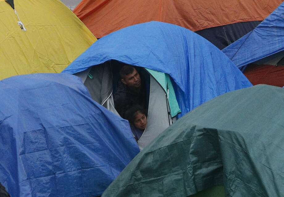 People peer from a tent at police talking with other migrants inside the Barretal migrant shelter in Tijuana. Photo: Rebecca Blackwell / Associated Press