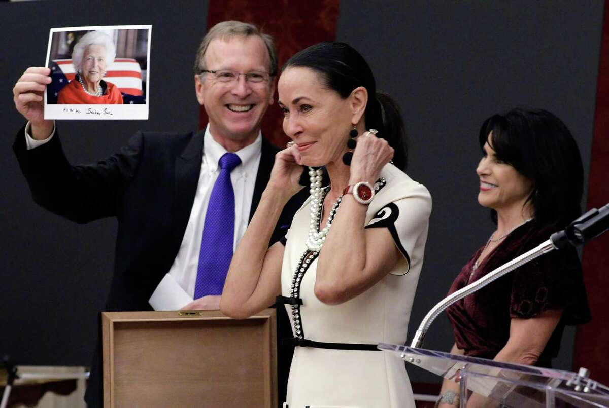 """Neil Bush holds a photo of his mother, former first lady Barbara Bush wearing the same pearl necklace that Sue Smith models that was given to Sue by her husband as Maria Bush looks on at the Barbara Bush Literacy Foundation's """"Celebration of Reading"""" party at the home of Sue and Lester Smith in Houston, TX, Dec. 7, 2017."""
