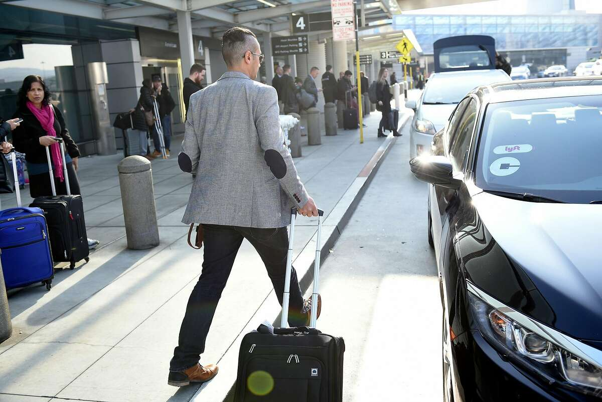 David Yanni, arriving from Los Angeles, walks his bag to the Lyft car picking him up at San Francisco International Airport in San Francisco, Calif., on Wednesday December 13, 2017.