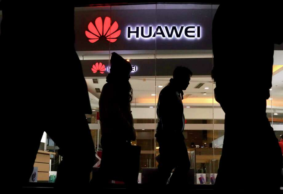 Pedestrians walk past a Huawei retail shop in Beijing Thursday, Dec. 6, 2018. China on Thursday demanded Canada release a Huawei Technologies executive who was arrested in a case that adds to technology tensions with Washington and threatens to complicate trade talks. (AP Photo/Ng Han Guan) Photo: Ng Han Guan / Copyright 2018 The Associated Press. All rights reserved.