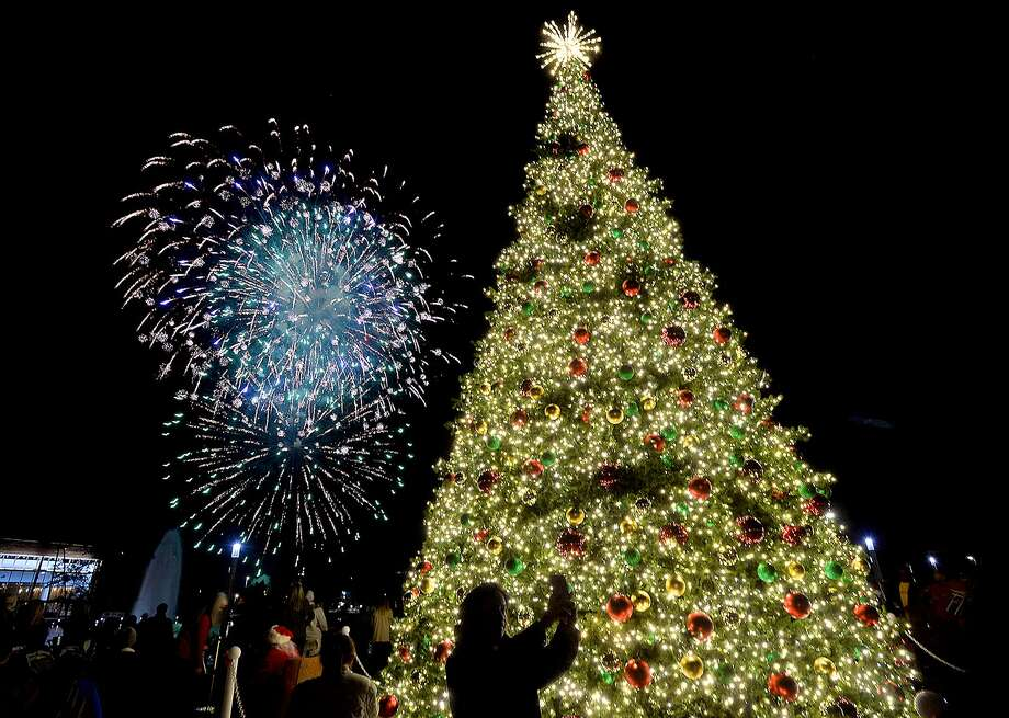 Attendees watch and take photos as fireworks light the sky behind Beaumont's giant lit Christmas tree at the Event Centre Wednesday. The holiday festival featured this year's large tree, holiday activities, visits with Santa, and fireworks.  Photo taken Wednesday, December 5, 2018  Kim Brent/The Enterprise Photo: Kim Brent / The Enterprise / BEN