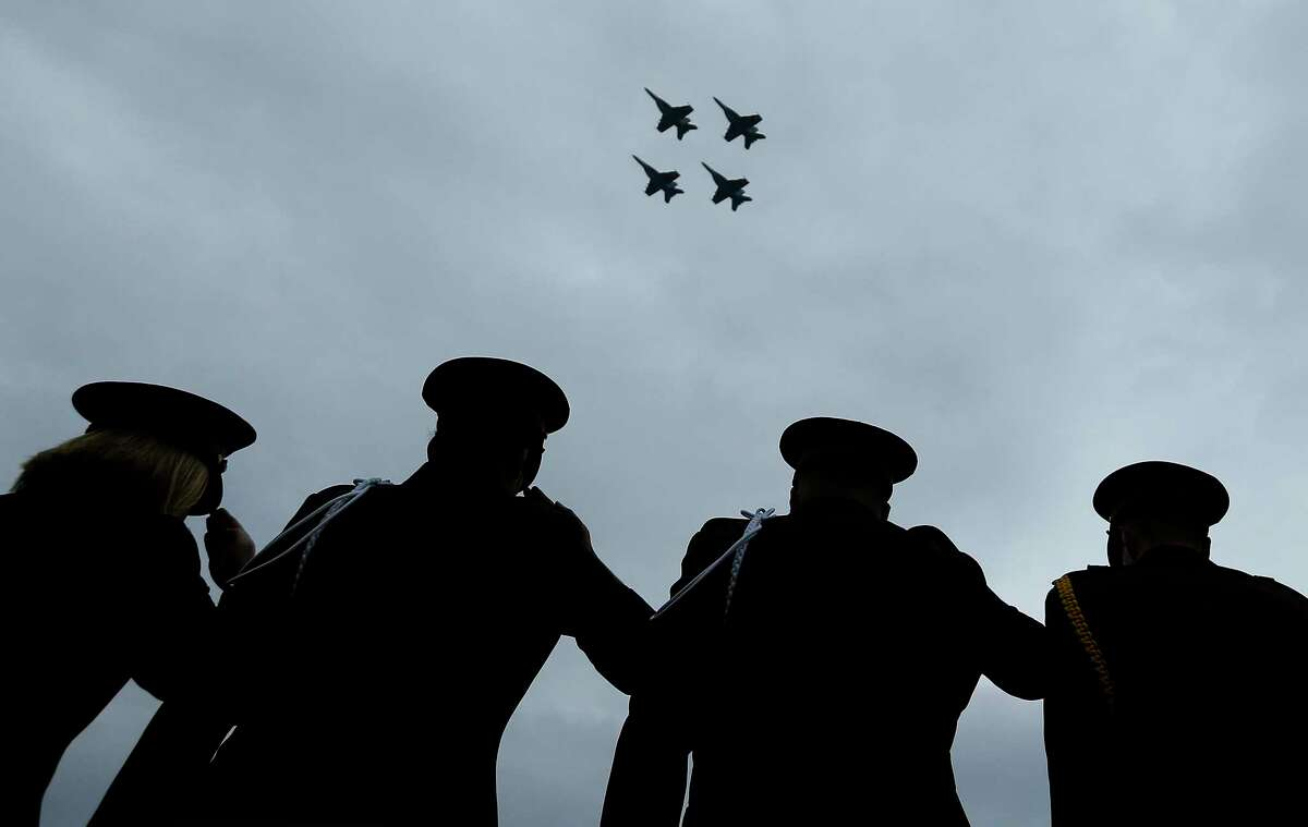 Texas A&M University Corps of Cadets salute as the Unites States Navy perform a 21-strike aircraft