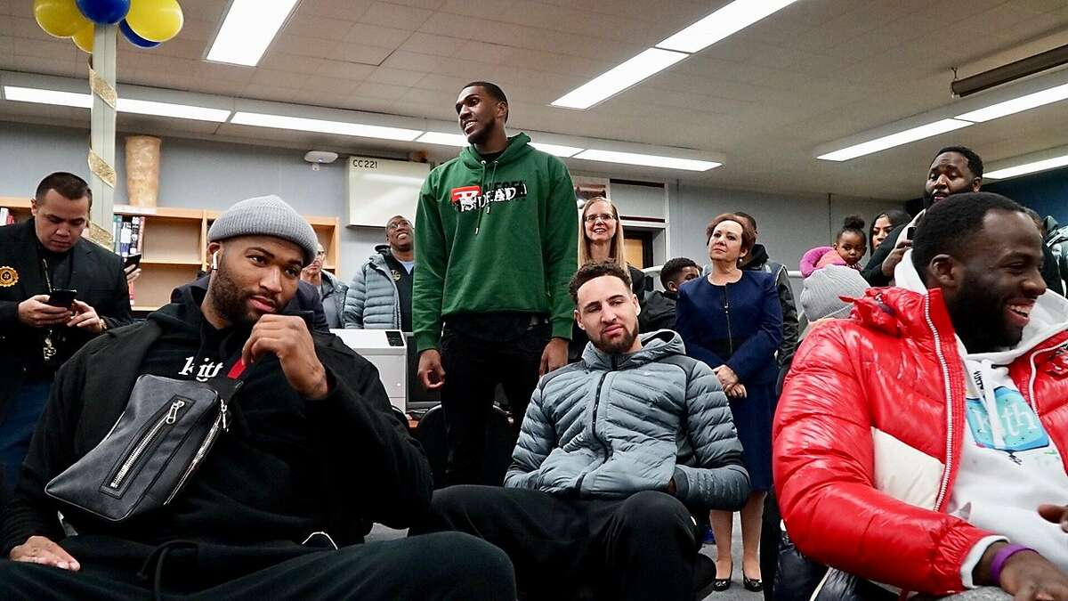 Warriors center Kevon Looney, surrounded by his Golden State teammates, speaks to students at his alma mater, Alexander Hamilton High School, in Milwaukee.