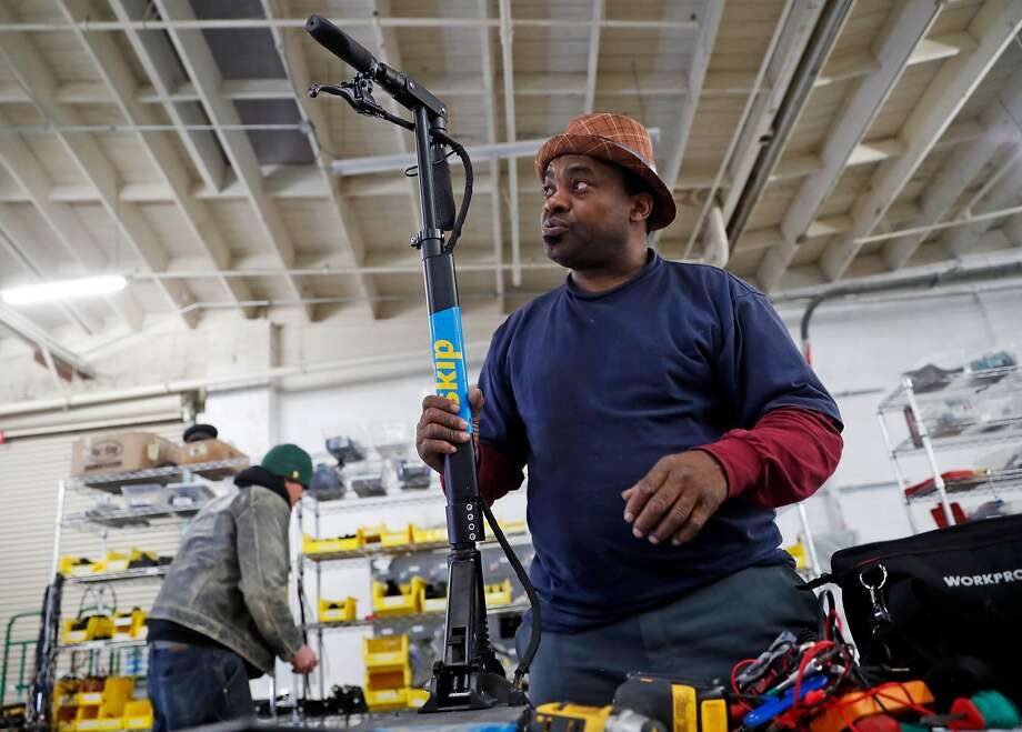 James, formerly homeless, repairs a scooter at the Skip workshop, where he earns $22 an hour as a technician. Photo: Scott Strazzante / The Chronicle