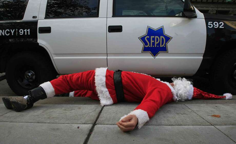 A man dressed as Santa Claus lies next to a San Francisco Police car after Santa Con patrons were pushed out of Union Square in preparation for a possible protest during the 20th Annual SantaCon in San Francisco, Calif. Saturday, December 13, 2014. Photo: Jessica Christian / The Chronicle