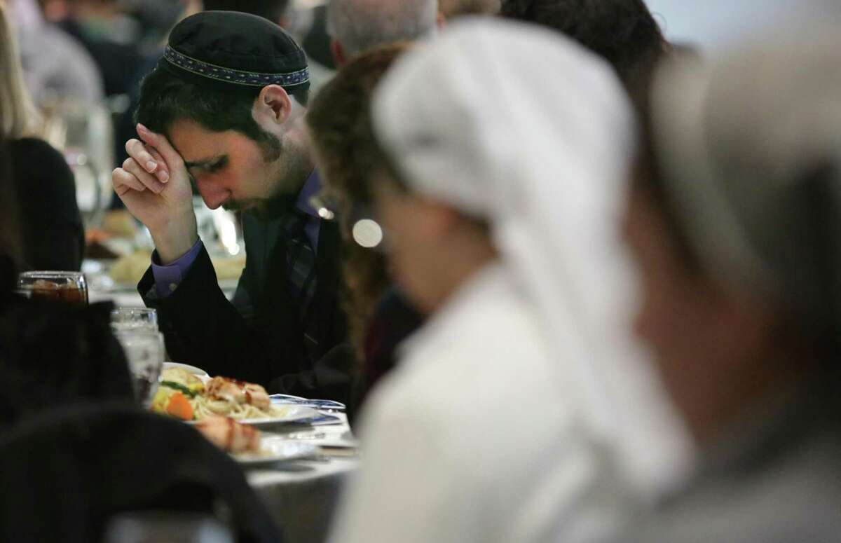 Rabbi Ben Richards, left, of Los Angeles, Catholic nuns, and others pray before eating lunch celebrating Hanukkah. Catholics and Jews gathered, on Thursday, Dec. 6, 2018, for their 17th annual Hanukkah celebration at San Fernando Cathedral Hall.