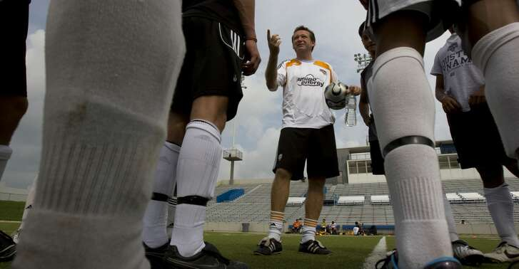 A group of players with the Houston Dynamo Academy listen as James Clarkson, (center) Dynamo director of youth development, gives instruction during a practice held at Delmar Stadium Wednesday, July 29, 2009, in Houston.  The academy team will be headed to Europe next week to play six games against the developmental teams for the Rangers FC, Celtic FC, FC Barcelona, and Real Madrid CF.  The Houston Dynamo Academy train's and develops local soccer players 18 and under in technical, social, psychological and the physical aspects of the game. ( Johnny Hanson / Chronicle )