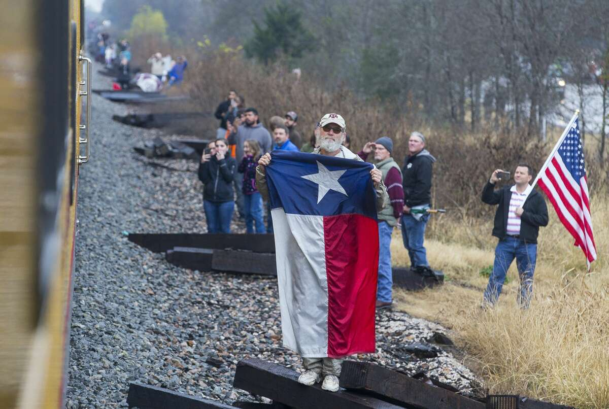 People watch along the route as the train carrying former President George H.W. Bush travels from Houston to College Station for President Bush's burial, Thursday, Dec. 6, 2018.