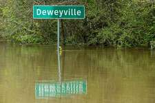 ADeweyvillecity sign stands half submerged in floodwaters from the Sabine River on Wednesday, March 16, 2016, inDeweyville. ( Brett Coomer / Houston Chronicle)