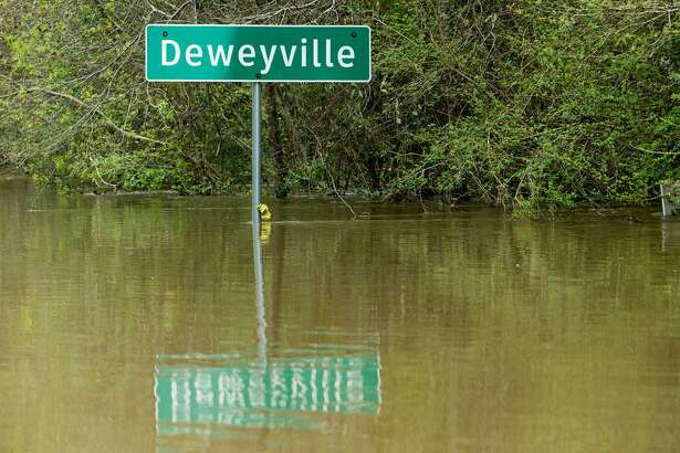 A Deweyville city sign stands half submerged in floodwaters from the Sabine River on Wednesday, March 16, 2016, in Deweyville. ( Brett Coomer / Houston Chronicle)