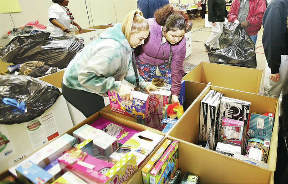 Alton High School juniors Aaliyah Jones, left, and Sandy Graves, right, sort donated items to the United Way's Community Christmas Thursday in the Main Street United Methodist Church in Alton. The items will be delivered today to 16 United Way organizations. Photo: John Badman | The Telegraph